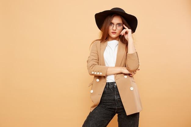 Bella ragazza bruna con i capelli lunghi con gli occhiali e un cappello nero in testa vestita con t-shirt bianca, jeans e giacca beige è in posa sullo sfondo beige in studio.