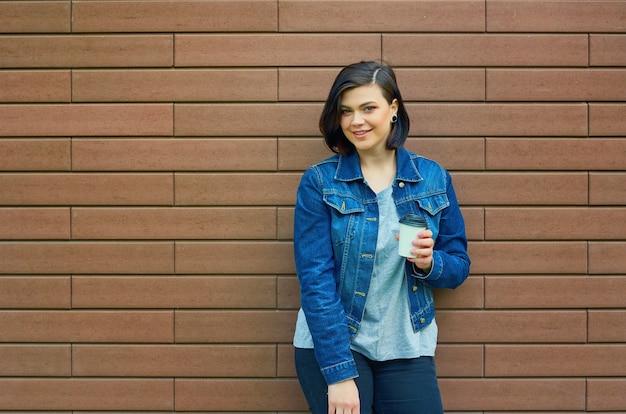 Bella ragazza mora con tunnel nelle orecchie in una giacca di jeans blu con una tazza di caffè in piedi davanti al muro di mattoni.