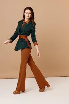 Moda abbastanza bruna trucco vestito in posa sfondo beige. foto di alta qualità