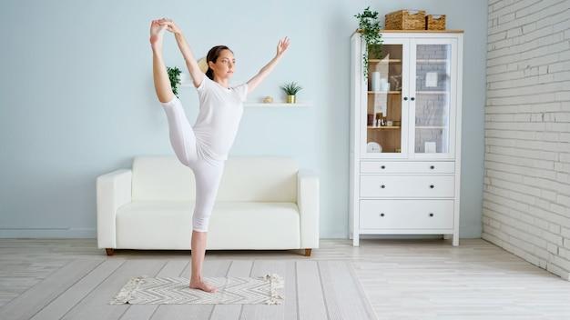 La donna incinta graziosa castana fa la posizione di utthita padangusthasana che pratica lo yoga vicino al sofà e all'armadietto del progettista nella stanza spaziosa a casa