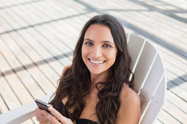 Abbastanza castana che si siede su una sedia e che manda un sms con il suo telefono cellulare