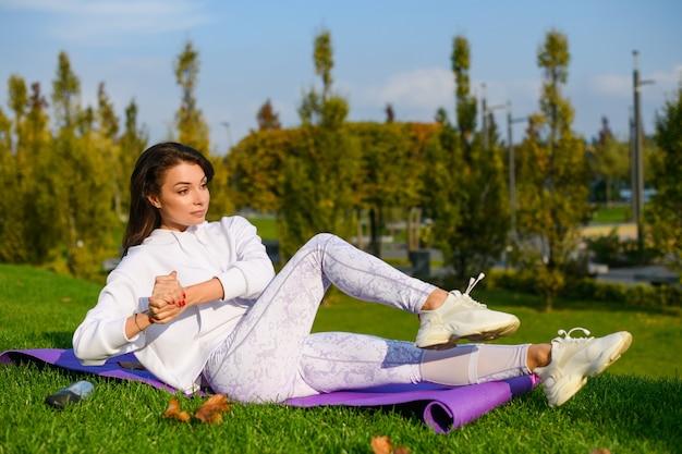 Una bella donna sportiva bruna si sdraiava sul tappetino durante la soleggiata giornata verde e faceva scricchiolii addominali fitness con i palmi delle mani chiusi