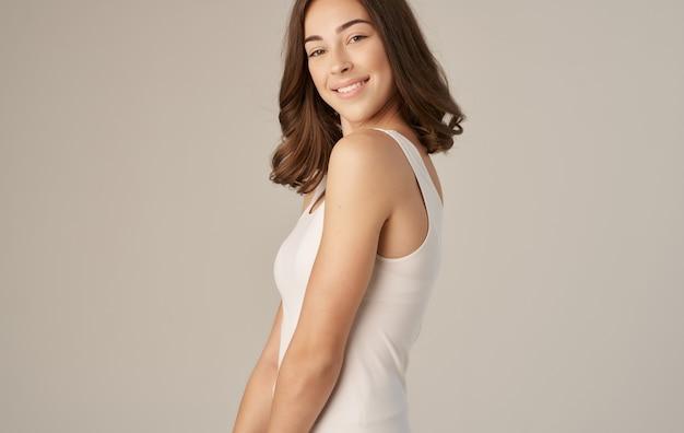 Bella mora in maglietta bianca sorride emozioni beige.