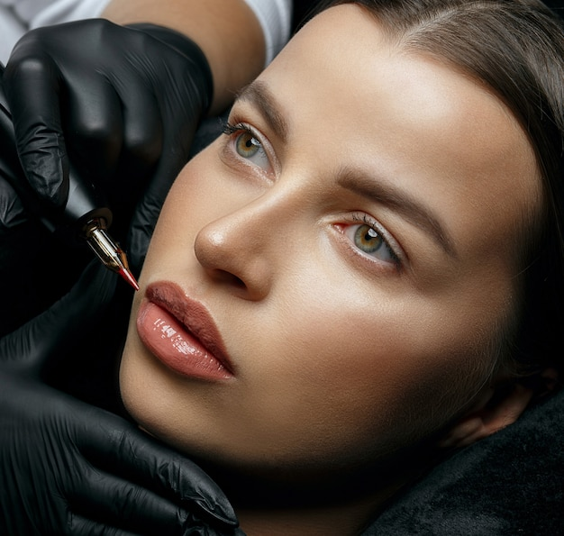 Donna abbastanza castana che ha procedura permanente del labbro al salone di bellezza. primo piano