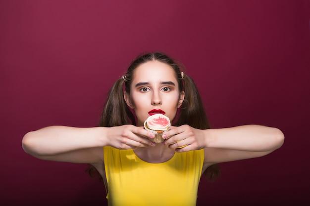 Bella donna castana che tiene un delizioso dessert con crema su uno sfondo rosso