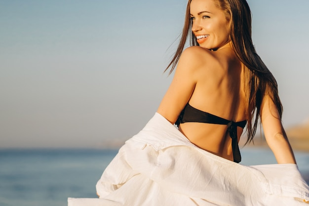 Donna graziosa del brunette che si distende sulla spiaggia al mare.