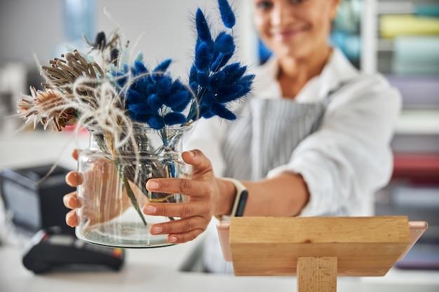 Bella donna bruna che mostra un vaso con fiori