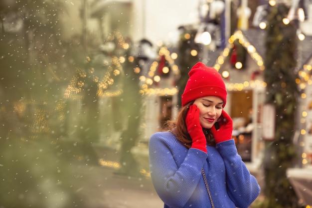 Una bella donna castana indossa un berretto rosso e un maglione blu che cammina alla fiera di natale nella piazza centrale della città. spazio per il testo