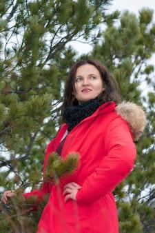 Bella donna bruna con lunghi capelli ricci vestita con una giacca invernale rossa e una sciarpa nera intorno al collo, in piedi nella foresta di pini