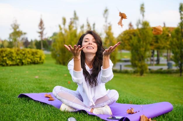 Una giovane donna graziosa si siede al tappetino sportivo con le gambe incrociate e gioca con le foglie secche al parco cittadino durante l'autunno