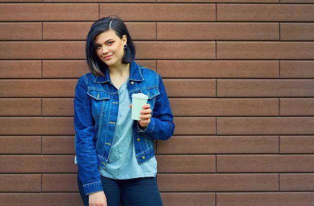 Giovane donna abbastanza mora con tunnel nelle orecchie in una giacca di jeans blu con una tazza di caffè in piedi davanti al muro di mattoni.