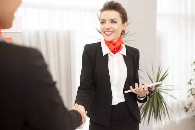 Agente di affari grazioso che agita le mani con il cliente