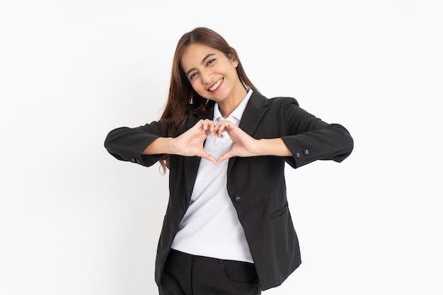 Bella donna d'affari che fa un gesto di cuore con le dita davanti al petto mostrando il suo amore