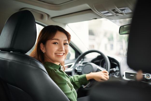 Bella donna d'affari che sorride e guida nella sua auto