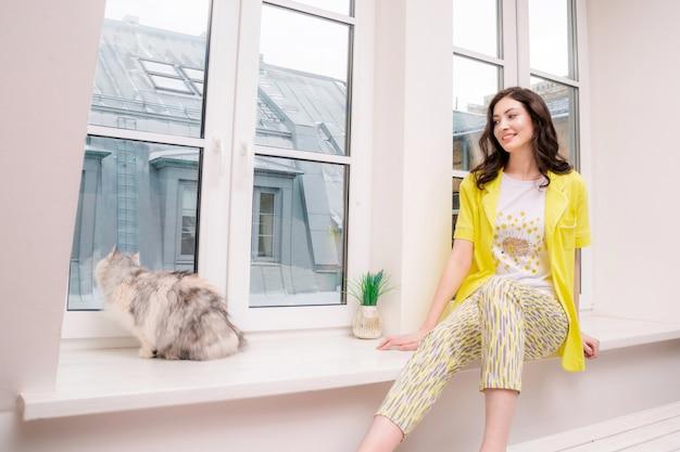 Donna castana abbastanza caucasica che si siede sul davanzale di una finestra e guarda il suo gatto che guarda fuori.