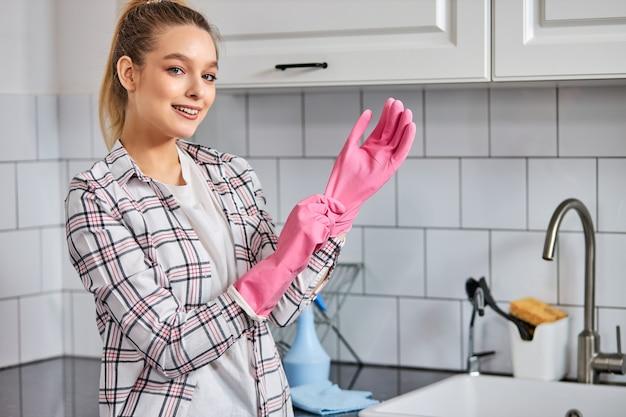 Donna abbastanza caucasica che indossa guanti di gomma prima di pulire la cucina lavando i piatti
