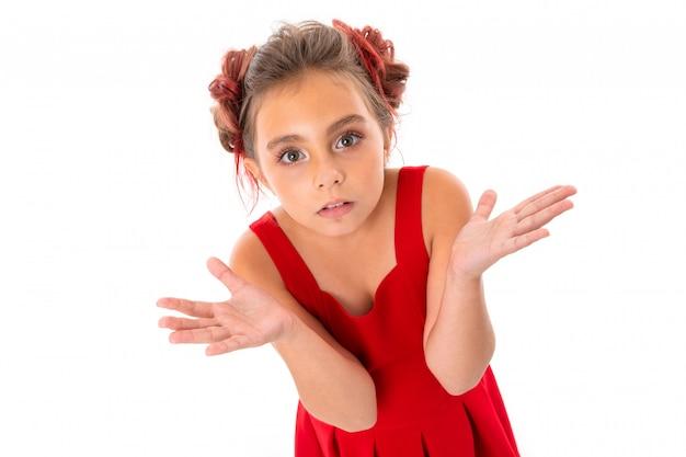 La ragazza abbastanza caucasica in vestito rosso non sa che cosa fare isolata sulla parete bianca