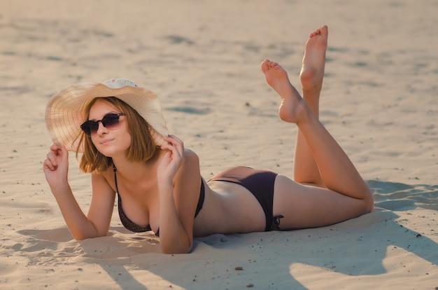 Ragazza snella abbastanza caucasica in occhiali e cappello sulla spiaggia, sdraiata sulla sabbia dorata. ricreazione e coccole in riva al mare (oceano, fiume, lago) in estate e nelle giornate di sole.