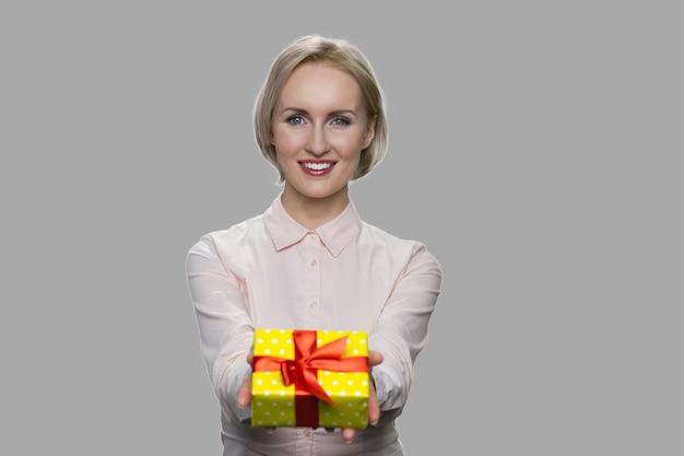 Donna abbastanza caucasica che dà confezione regalo. giovane bella donna d'affari consegna casella presente su sfondo grigio. offerta bonus speciale.