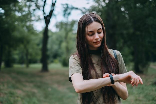 La donna abbastanza caucasica utilizza il fitness tracker durante l'allenamento sportivo nel parco.