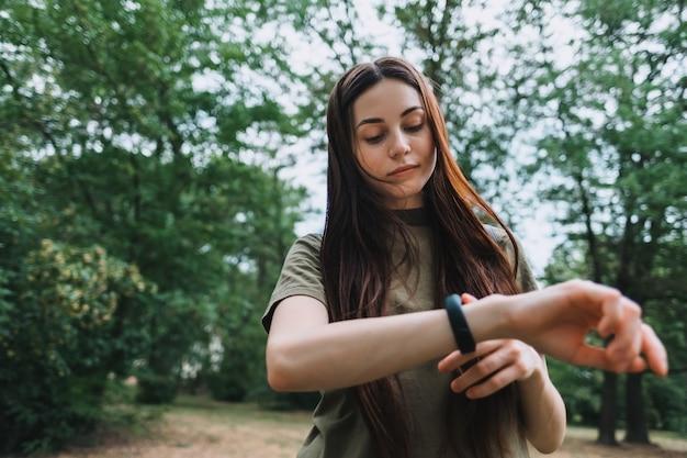 La donna abbastanza caucasica utilizza il fitness tracker durante l'allenamento sportivo.