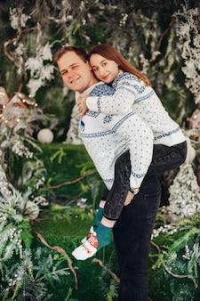 Bella donna caucasica con il marito gioire insieme alle decorazioni natalizie