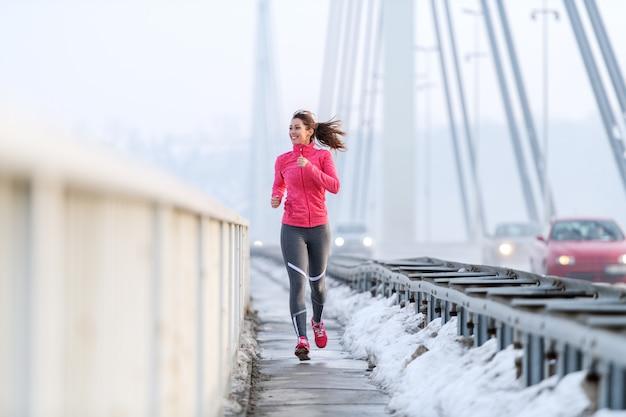 La donna abbastanza caucasica con la coda di cavallo si è vestita in abiti sportivi che corrono sul ponte all'inverno. concetto di stile di vita sano.
