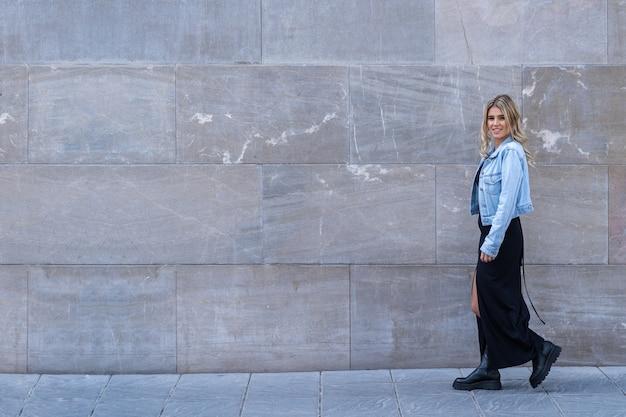 Bella giovane donna caucasica in abito nero e giacca di jeans che cammina con lo sfondo di un muro