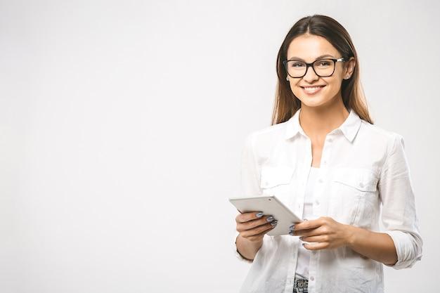 Donna alla moda fiduciosa abbastanza affascinante in camicia classica con tablet nelle mani