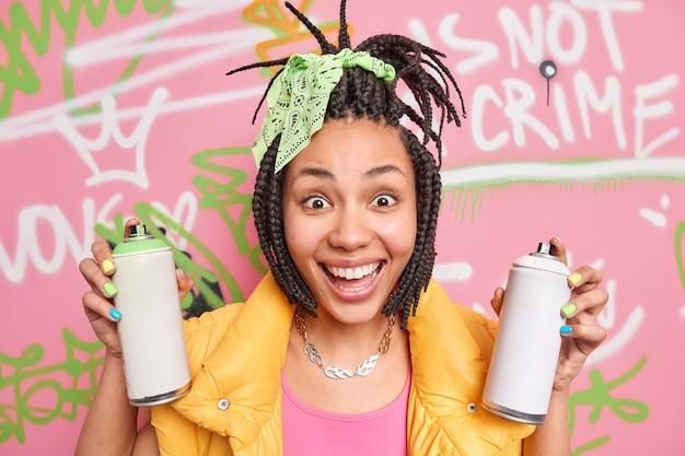 Abbastanza allegra ragazza afroamericana hipster con sorrisi dreadlocks detiene ampiamente due bottiglie di aerosol si sente felice e positivo utilizza spray aerosol per disegnare graffiti