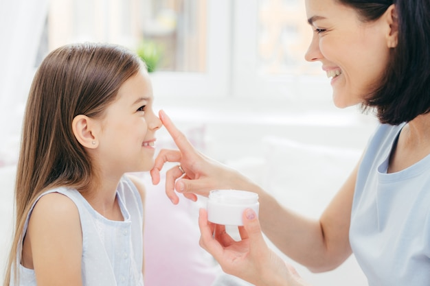 La femmina abbastanza allegra riceve la procedura di bellezza dalla madre affettuosa. la giovane donna attraente applica la crema di bellezza sul naso del `s della figlia