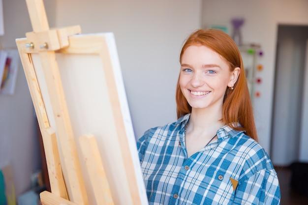 Piuttosto allegra giovane pittrice in camicia a scacchi che dipinge in studio d'arte