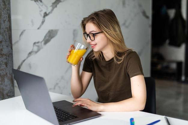 Giovane donna abbastanza allegra mentre è seduta al tavolo della cucina, lavorando al computer portatile, bevendo succo