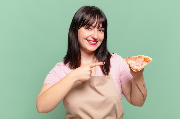 Donna graziosa chef che indica o mostra e tiene in mano una pizza