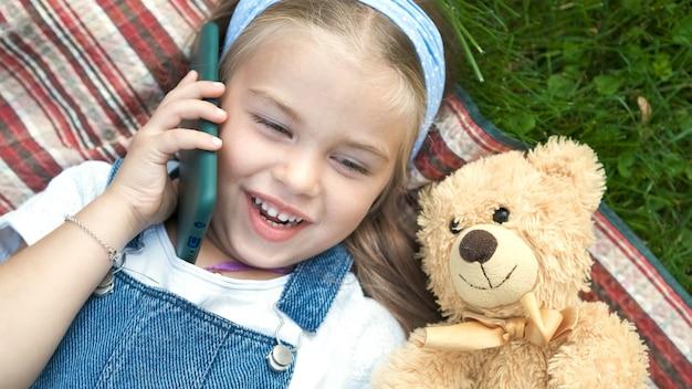 Ragazza graziosa del bambino che pone sul prato inglese verde con il suo orsacchiotto che parla sul telefono cellulare.