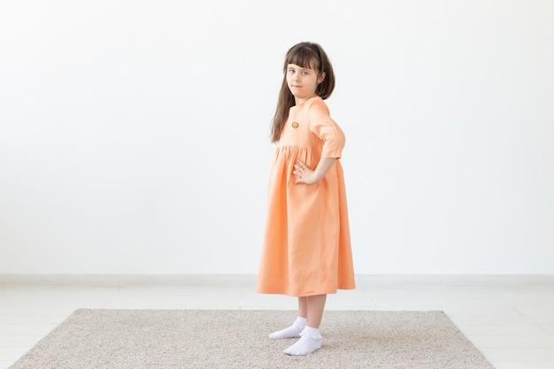 Ragazza graziosa del bambino che posa per la macchina fotografica, in un vestito corto arancione, muro bianco con lo spazio della copia