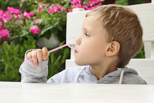 Il bambino grazioso tiene la paglia e distoglie lo sguardo si siede al tavolo del ristorante
