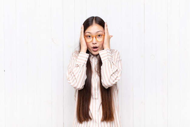 Bella donna cinese contro il muro bianco