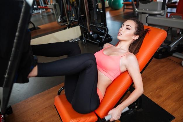 Giovane sportiva abbastanza concentrata che fa esercizi per le gambe usando attrezzature da palestra