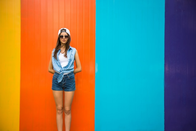 Ragazza abbastanza fredda in occhiali da sole e cappuccio in piedi contro. Foto Premium