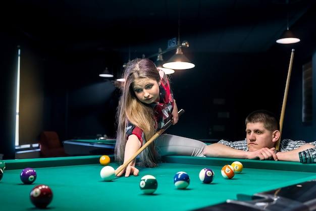 Bella coppia giocando a biliardo, uomo che si occupa di donna