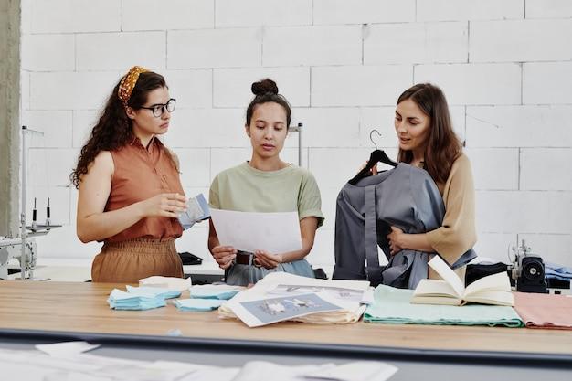 Designer piuttosto creativo o sarto che mostra ai suoi colleghi lo schizzo di moda durante la discussione delle caratteristiche delle nuove tendenze in base al posto di lavoro