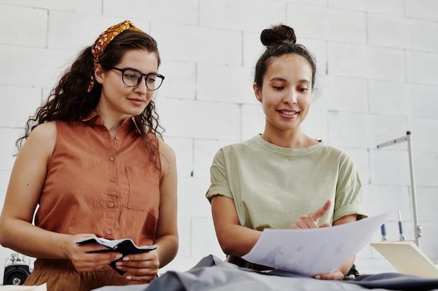 Donna abbastanza creativa che mostra il suo schizzo di moda collega e indica uno dei modelli durante la discussione delle caratteristiche delle nuove tendenze