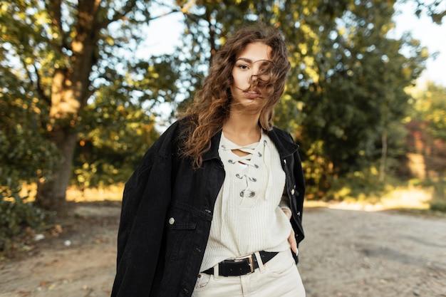 Una donna abbastanza riccia in abiti alla moda con giacca di jeans e camicetta lavorata a maglia cammina all'aperto nel parco