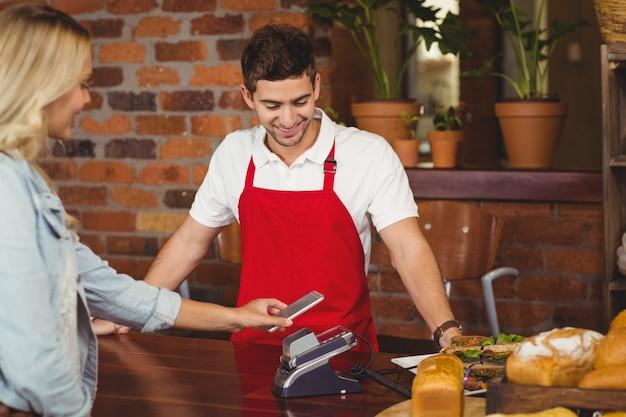 Grazioso cliente che effettua un pagamento mobile