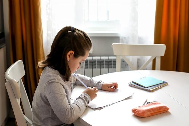 Studentessa carina 7-8 anni che studia a casa. scuola a casa, istruzione online, educazione domestica,