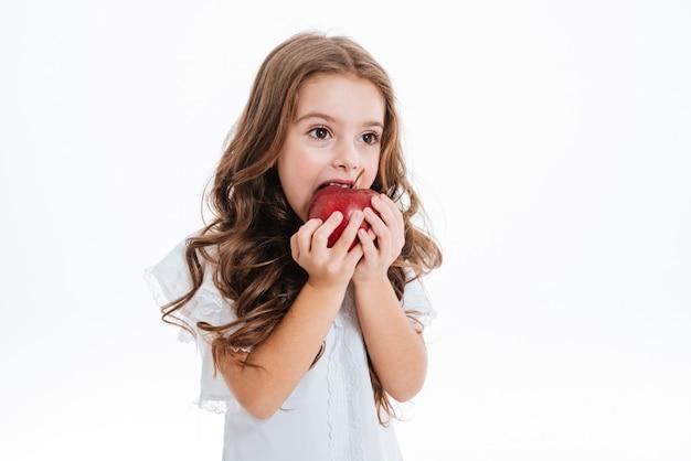 Bambina abbastanza carina che morde e che mangia mela rossa