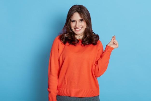 La donna dai capelli abbastanza scura con un sorriso piacevole rende coreano come il segno esprime amore, indossa un maglione casual isolato sopra il muro blu.