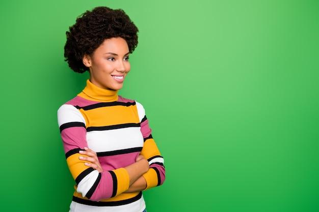 Di donna d'affari ondulata pelle abbastanza scura braccia incrociate alla ricerca di spazio vuoto ascoltare colleghi che incontrano sorriso amichevole indossare maglione a righe casual