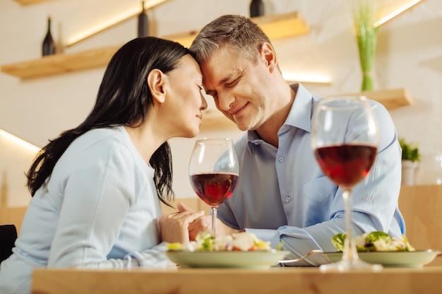 Donna abbastanza disabile e un uomo ben costruito sorridente attraente che si siedono in un caffè che cenano